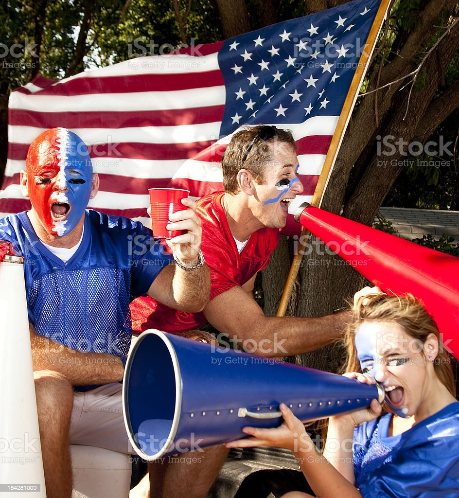 Group of excited football fans yelling at tailgate party. Flag. royalty-free stock photo