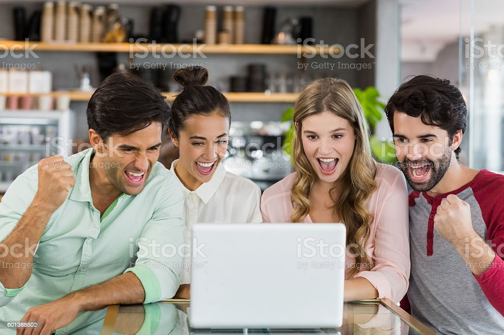 Group of excited friends using laptop in cafe