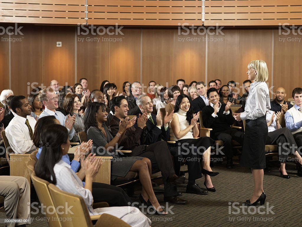 Group of executives applauding for woman leading seminar in auditorium stock photo