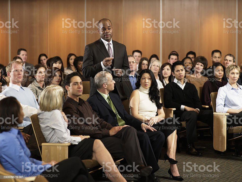 Group of executives listening to man leading seminar in auditorium royalty-free stock photo