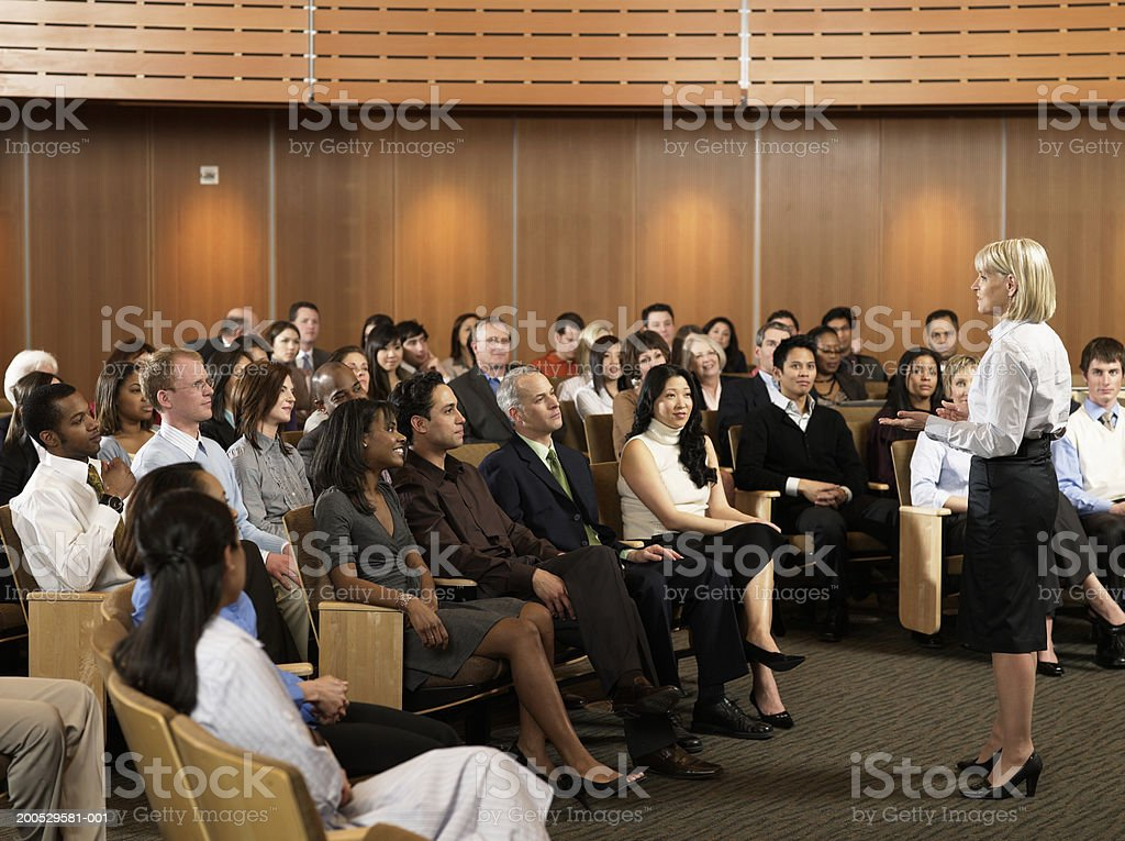 Group of executives listening to woman leading seminar in auditorium stock photo