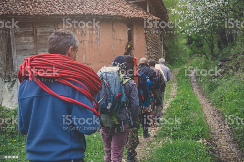 group of explorers hiking on an old dirt road . stock photo