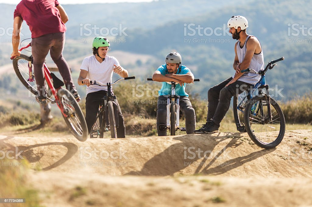 Group of extreme cyclists discussing while relaxing on dirt road. stock photo