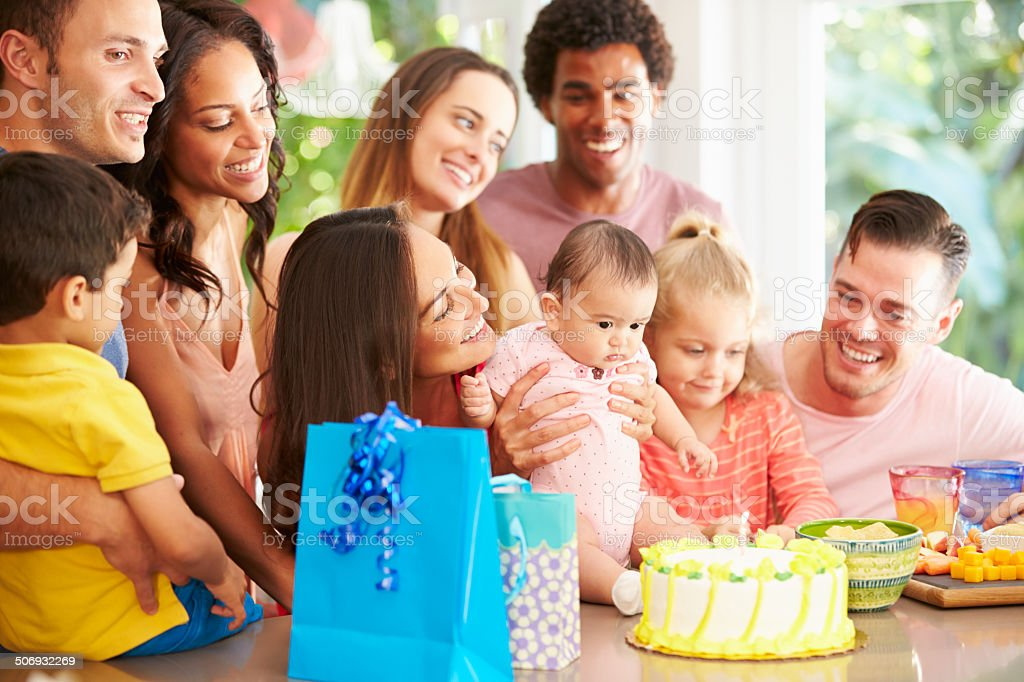 Group Of Families Celebrating Child's First Birthday At Home stock photo