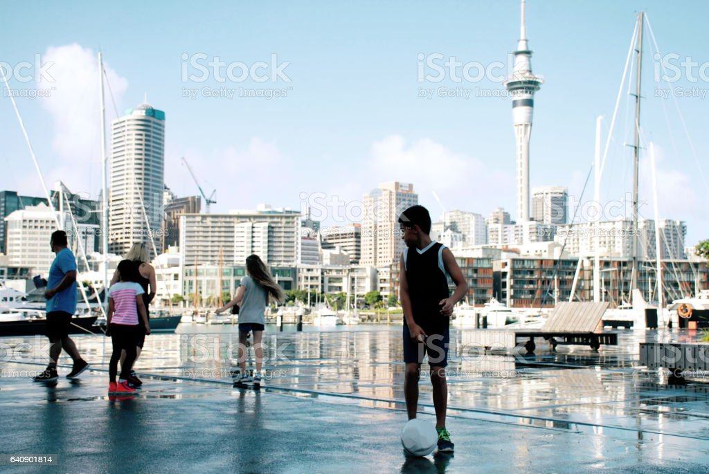 Group of Family Friends Play Soccer against a cityscape stock photo