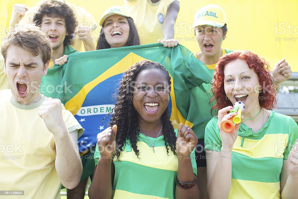 Group of fans cheering wearing green and yellow. royalty-free stock photo