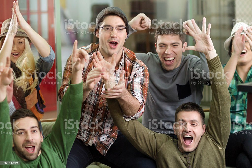 Group Of Fans Watching TV stock photo