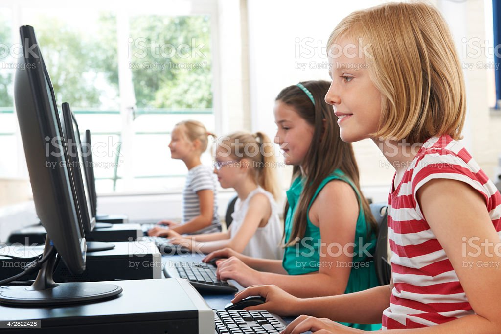 Group Of Female Elementary School Children In Computer Class stock photo