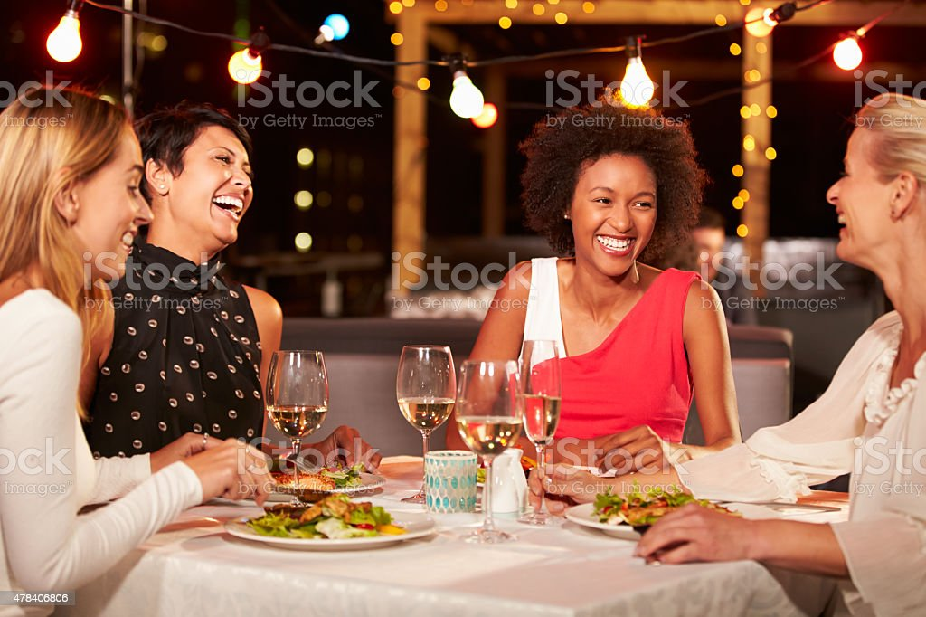 Group of female friends eating dinner at rooftop restaurant stock photo