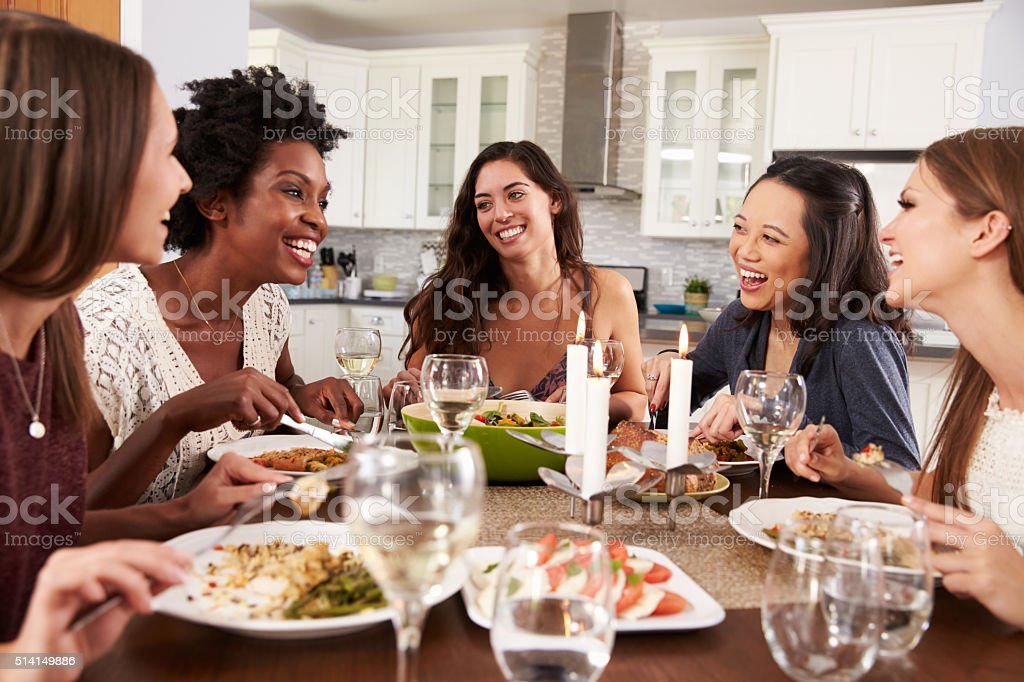 Group Of Female Friends Enjoying Dinner Party At Home stock photo