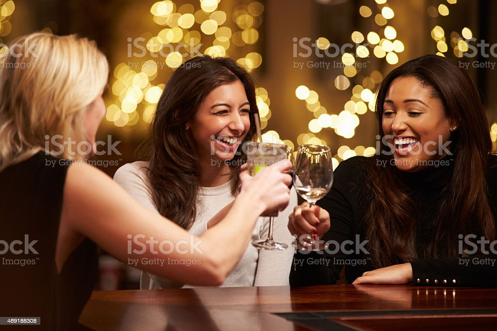 Group Of Female Friends Enjoying Evening Drinks In Bar stock photo