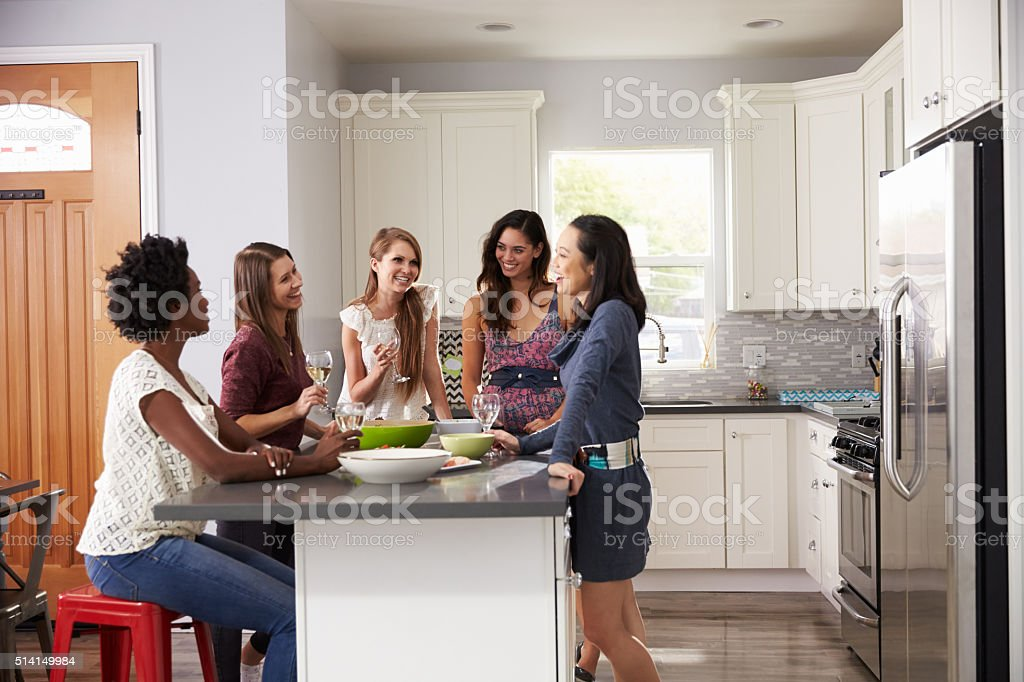 Group Of Female Friends Enjoying Pre Dinner Drinks At Home stock photo