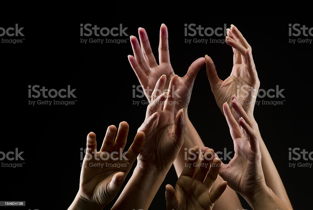 Group of female hands reaching towards the sky stock photo