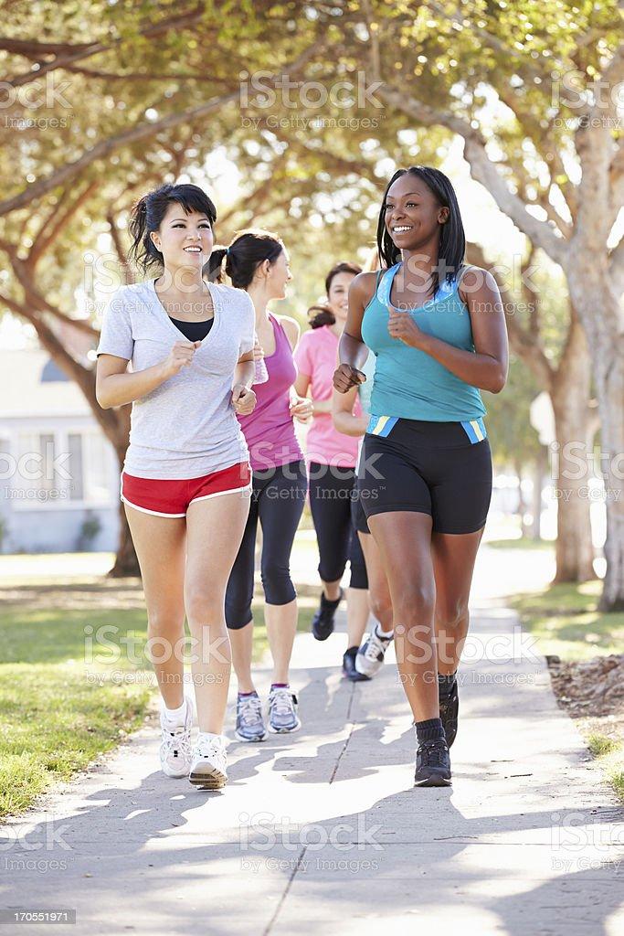 Group of female runners exercising on suburban street stock photo