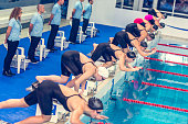Group of female swimmers jumping into the pool