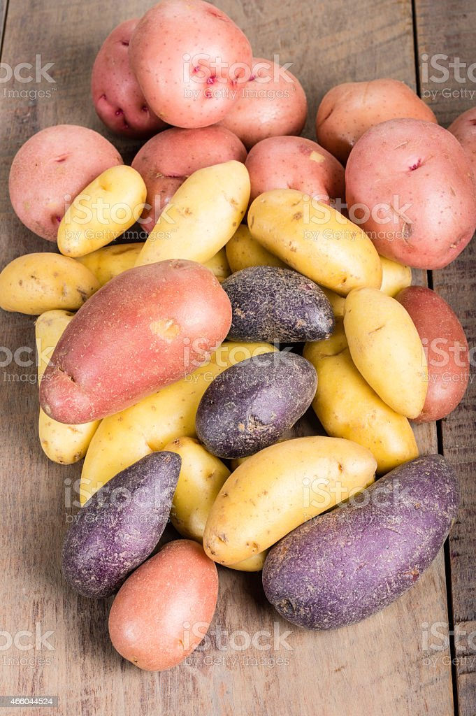 Group of fingerling potatoes on wooden table stock photo