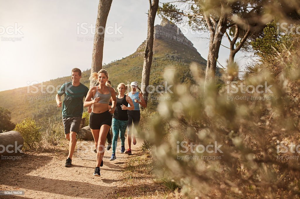 Group of fit people trail running on a mountain path stock photo