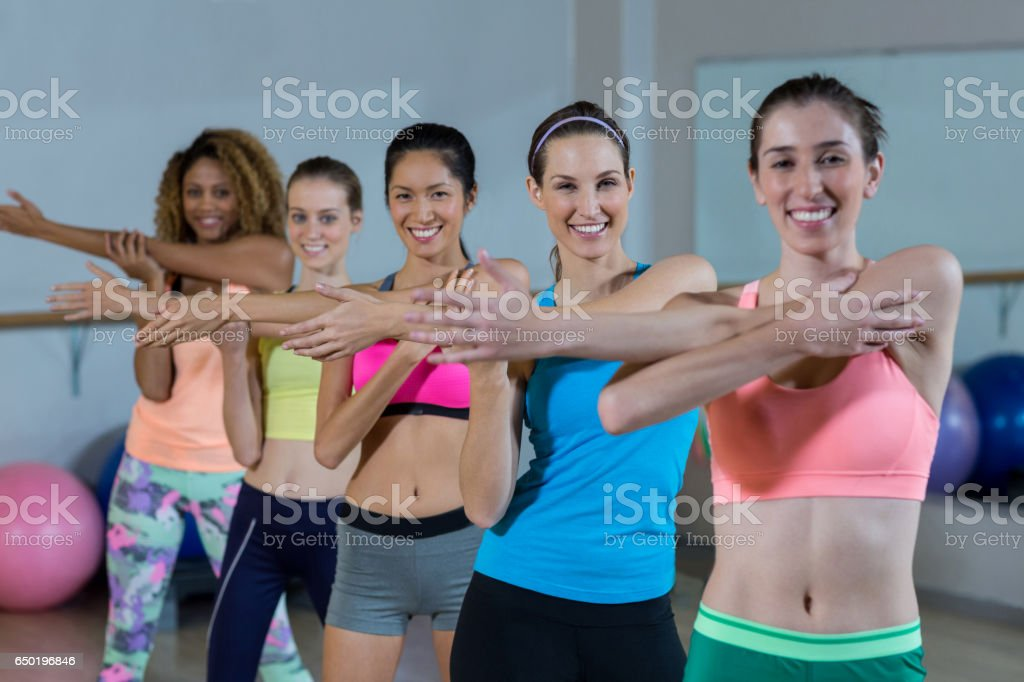 Portrait of group of fitness team performing stretching exercise in...