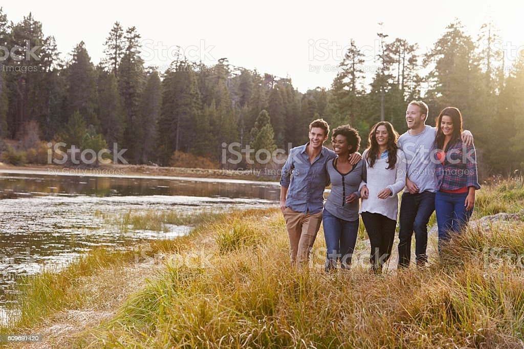 Group of five happy friends walking near a rural lake stock photo