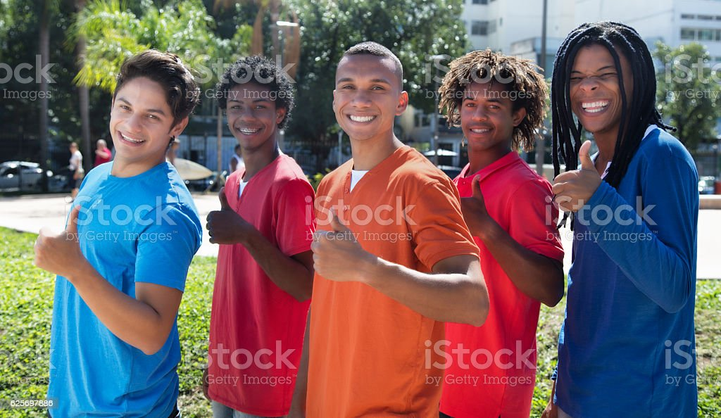 Group of five male young adults in line showing thumbs stock photo