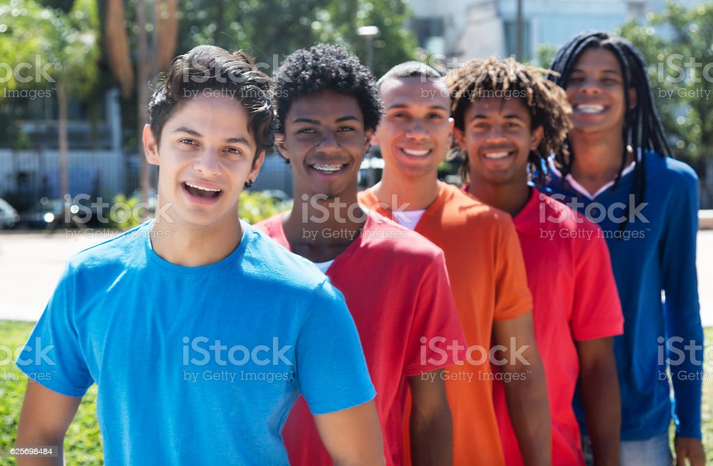 Group of five male young adults standing in line stock photo