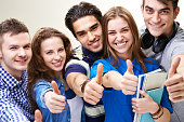 group of five students showing thumbs up