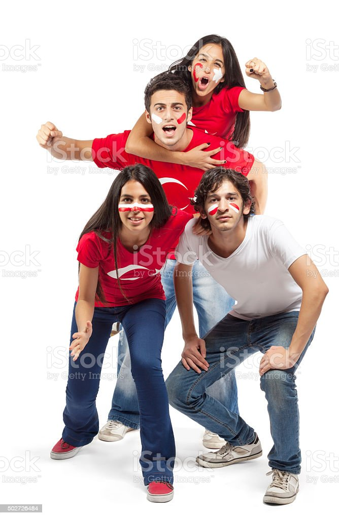 Group of football fans with their faces painted jumping stock photo