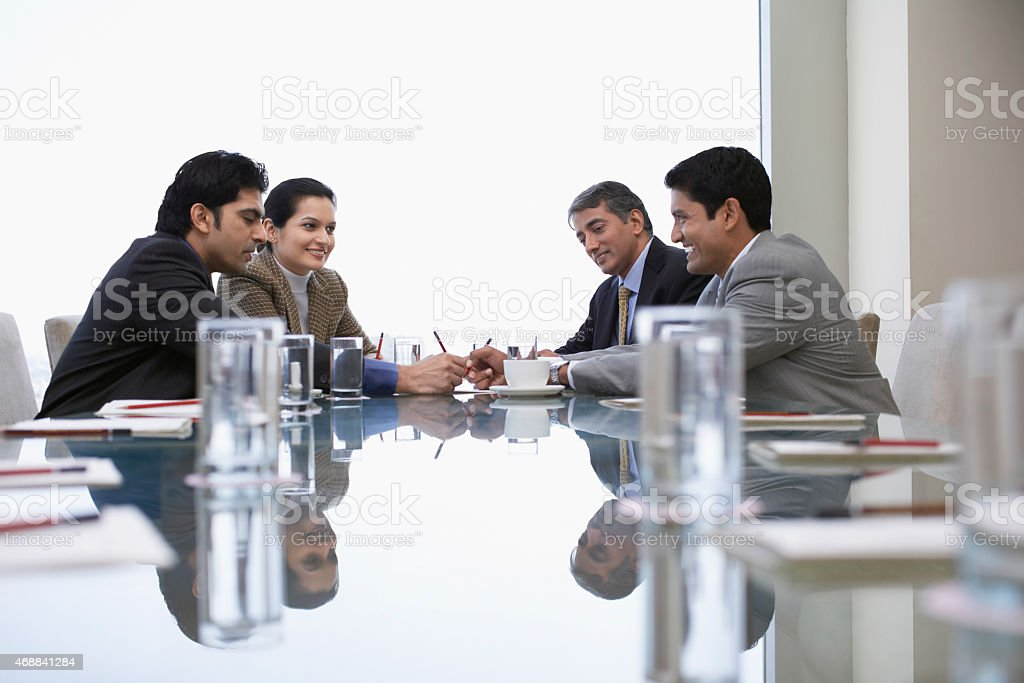 A group of four businesspeople talking at a table stock photo