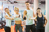 Group of four friends showing thumbs up in a gym.