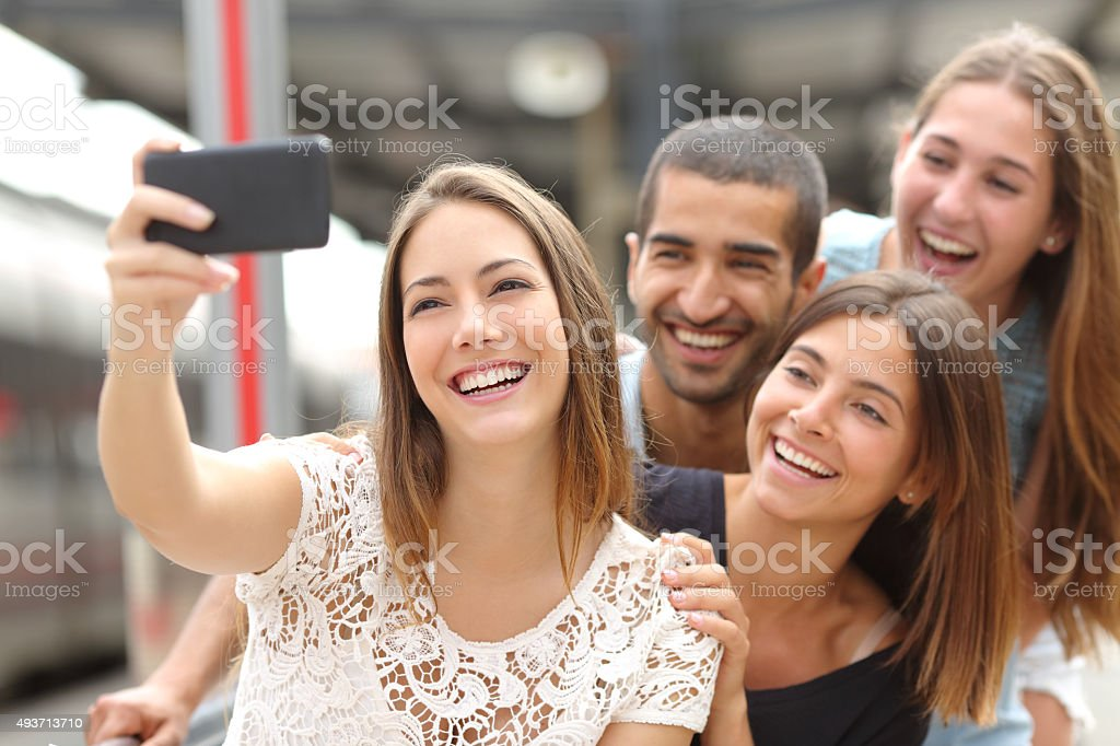 Group of four friends taking selfie with a smart phone stock photo