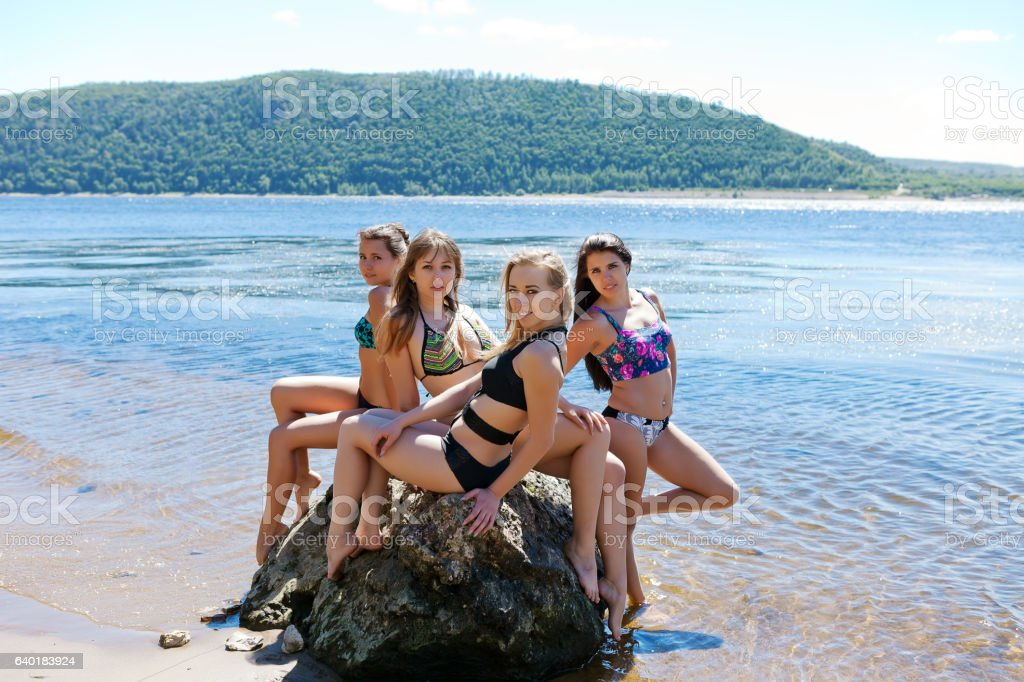 group of four girls in bathing suit on large stone stock photo