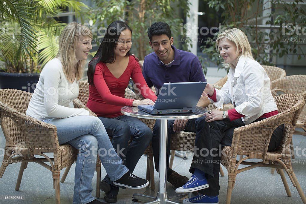Group of four multi-ethnic students in teamwork with laptop presentation royalty-free stock photo