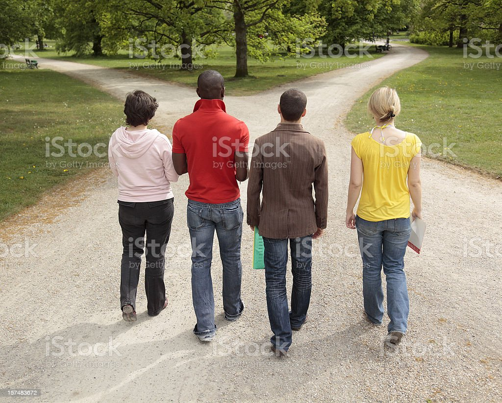 Group of four multi-ethnic students walking on forked footpath royalty-free stock photo
