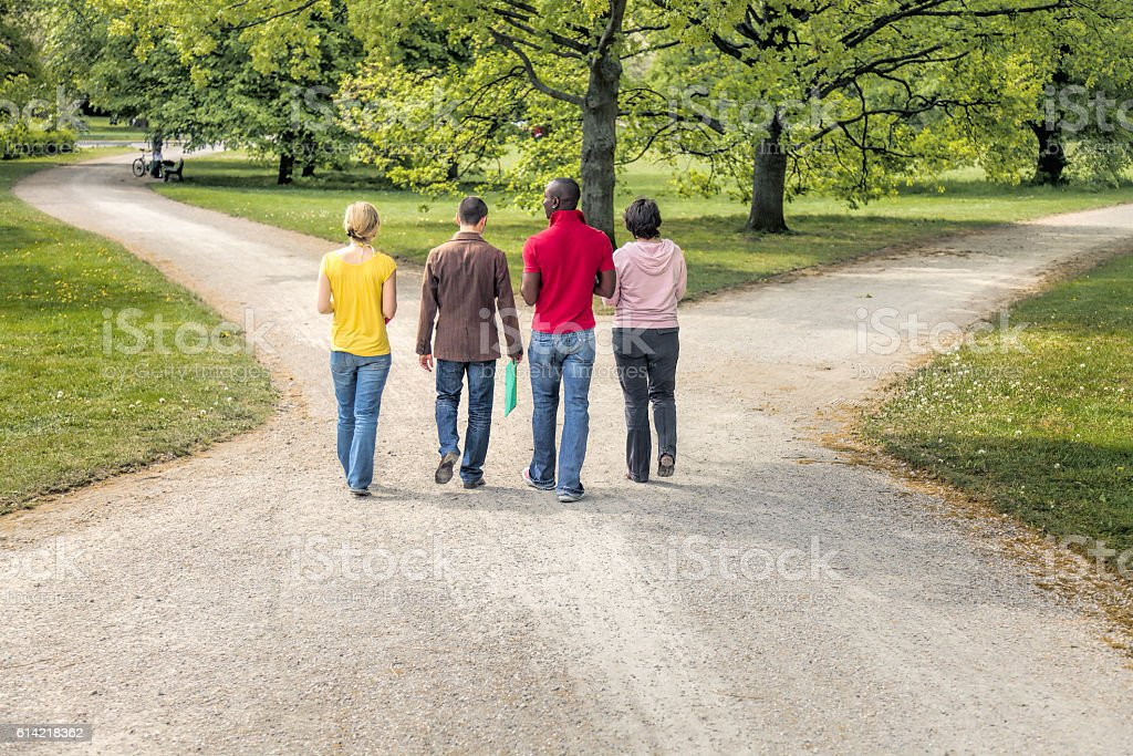 Group of four multi-ethnic students walking on forked footpath stock photo