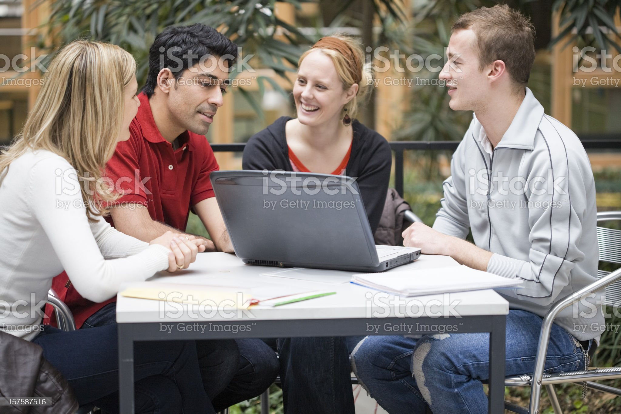 Group of four students in teamwork with laptop presentation royalty-free stock photo