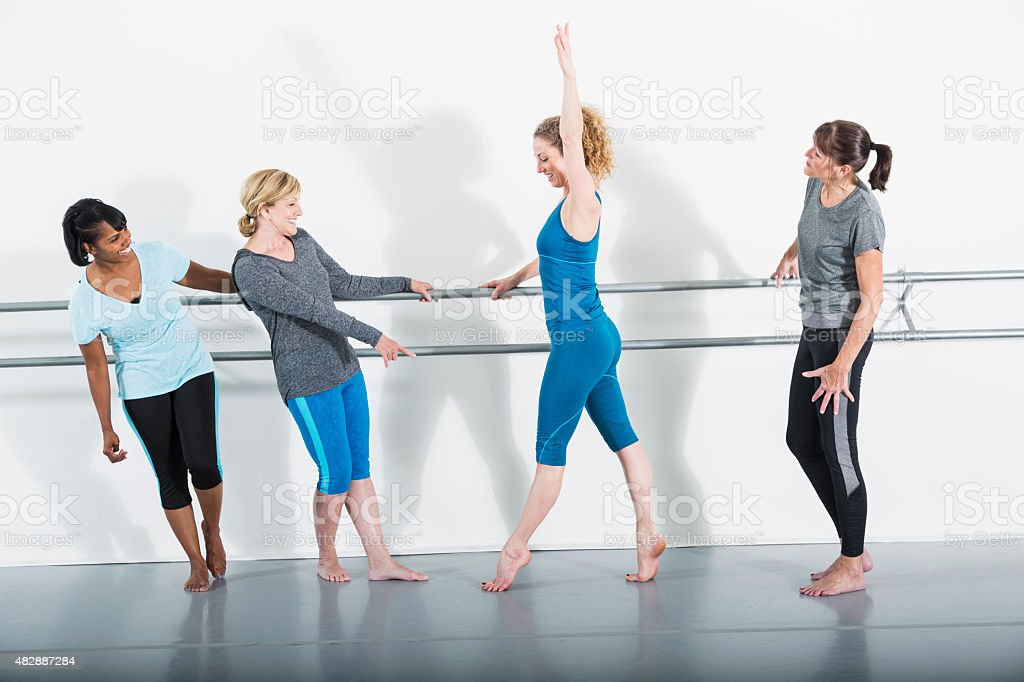 Group of four women in dance studio doing barre exercises stock photo