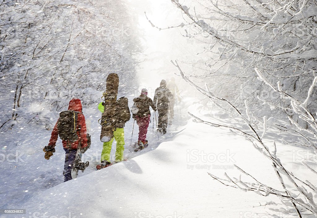Group of freeriders climbing up a winter trail stock photo