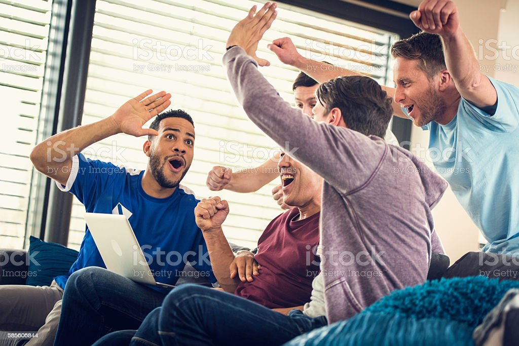 Group of frends watching game on laptop stock photo