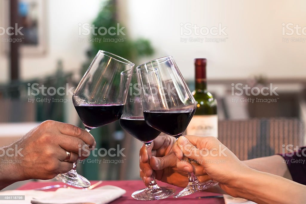 Group of friend clinking glasses of wine in a restaurant stock photo