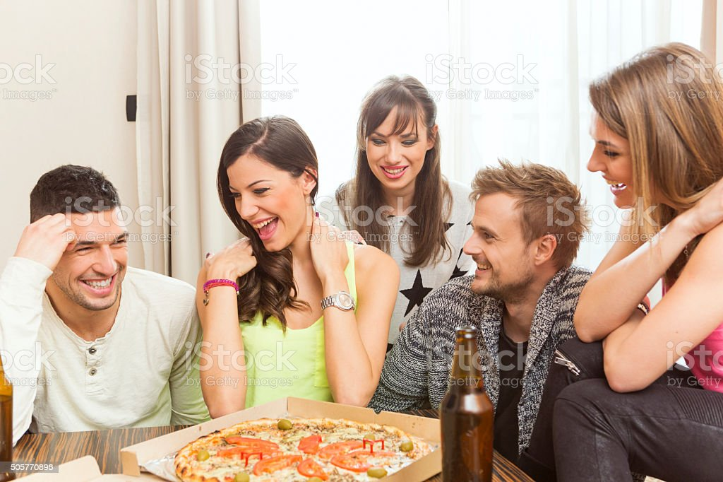Group of friend having beer and pizza at home stock photo
