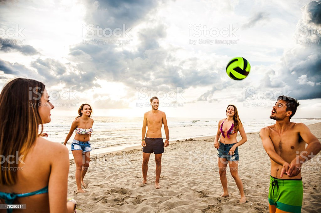 Group of friend play volley on the beach stock photo