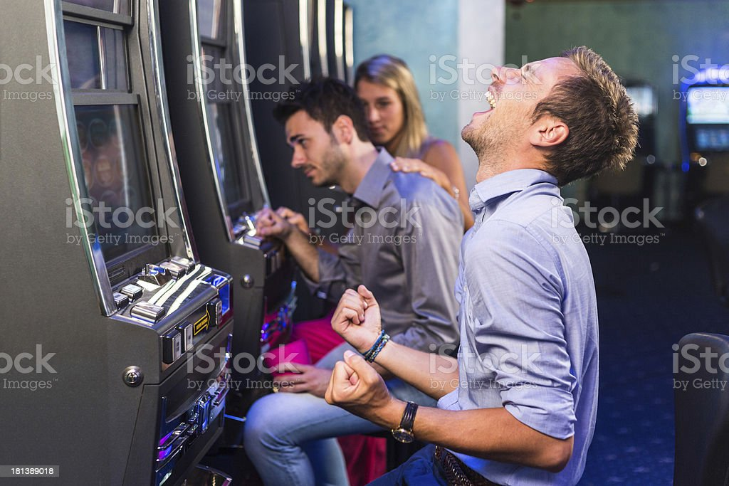 Group of Friend Playing with Slot Machines royalty-free stock photo