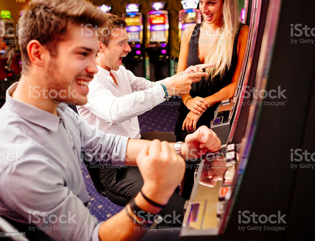 Group of Friend Playing with Slot Machines stock photo