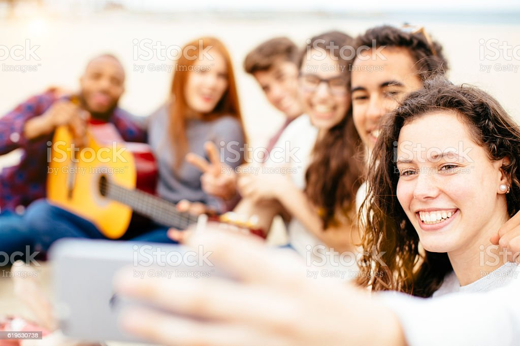 Group of friends and partying and singing in the beach. stock photo