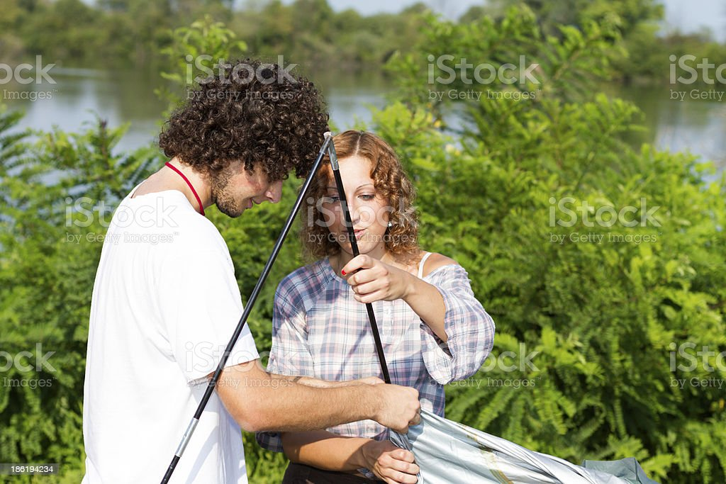 Group of friends assembles a tent royalty-free stock photo
