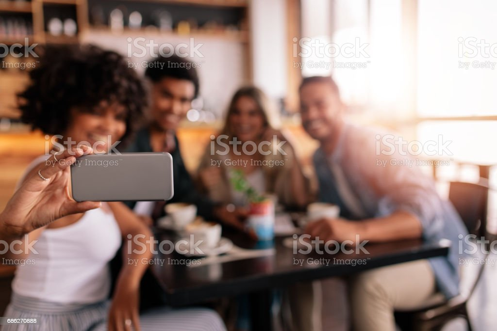 Group of friends at cafe taking selfie stock photo