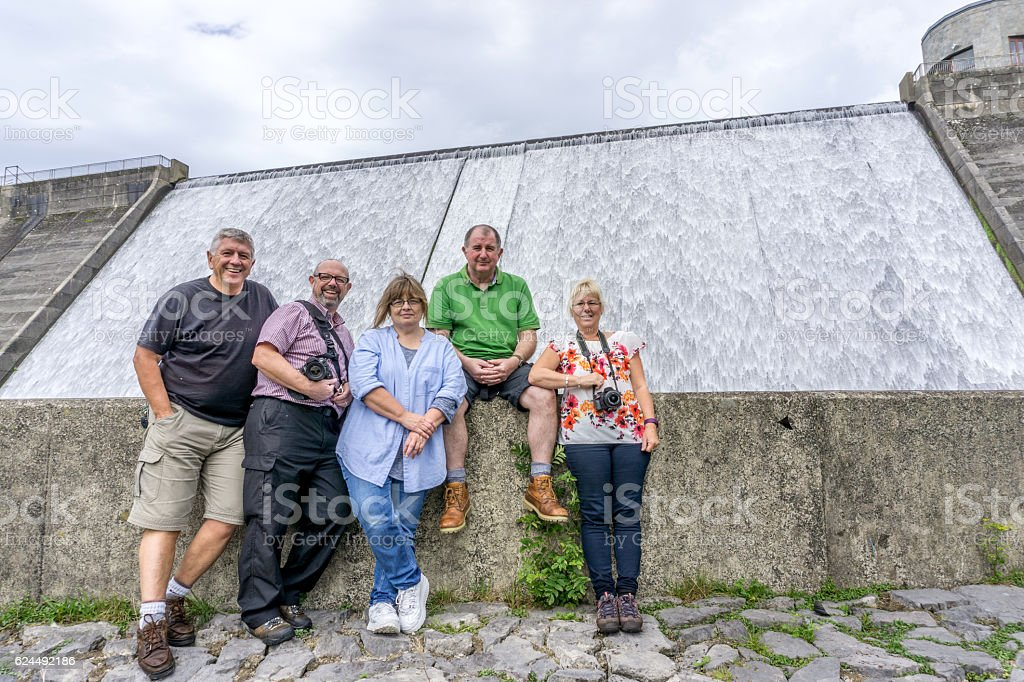 Group of friends at Reservoir overflow weir in Welsh countryside stock photo