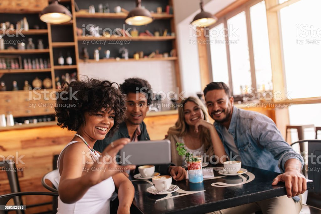 Group of friends at restaurant taking selfie stock photo