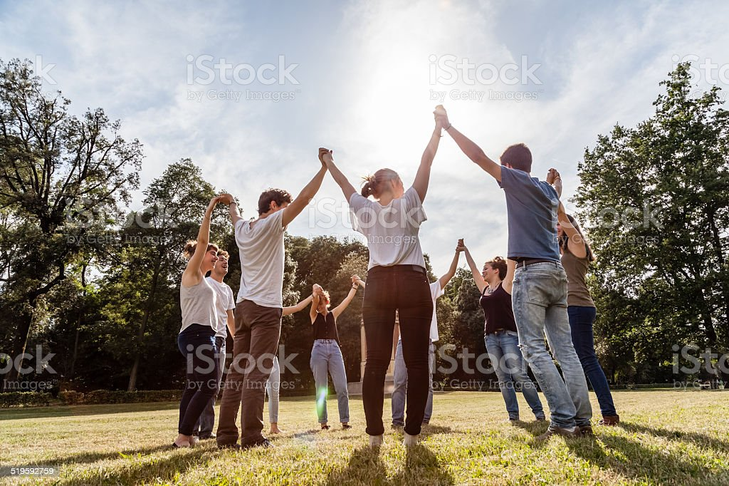 Group of friends at the park holding hands stock photo