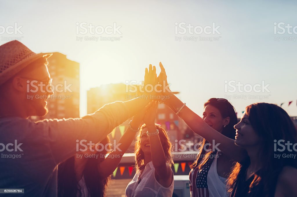Group of friends at the rooftop doing high five stock photo